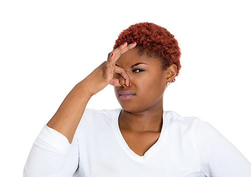 Bad breath, woman pinches her nose