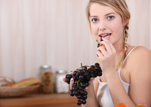 Woman eating grapes